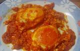 Fried eggs with tomatoes in olive oil